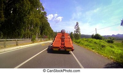 Following a truck car trailer in - Car traveling on a two...