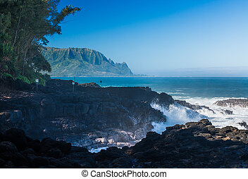 Waves hit rocks at Queens Bath Kauai - Waves crash into...
