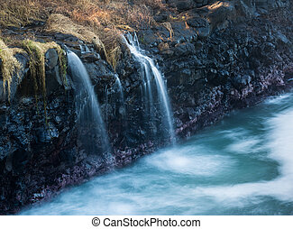 Waterfall flows into sea at Queens Bath Kauai - Waves crash...