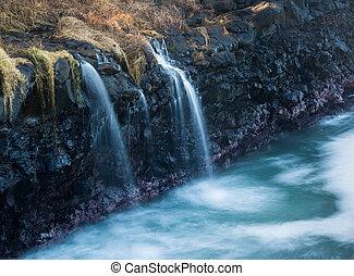 Waterfall flows into sea at Queens Bath Kauai - Waves crash...