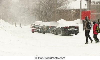 Two People going on the street in strong snow storm -...