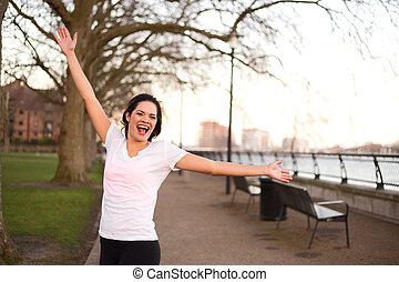 happy woman outdoors celebrating a fitness goal.