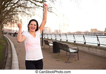 young woman outdoors celebrating a fitness goal