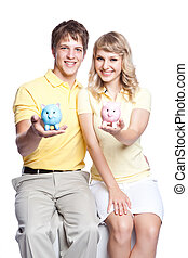 Young couple saving money - A young couple holding a piggy...