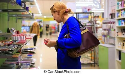 young blonde woman shopping in the womens cosmetics store,...