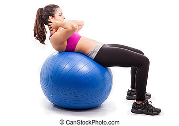 Doing crunches on exercise ball - Athletic and strong young...