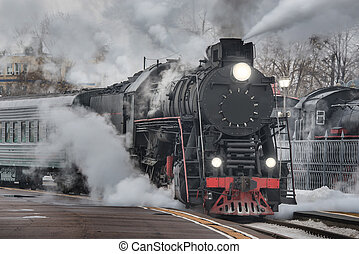 Retro steam train departs from the railway station at...