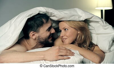 Carefree Couple in Bed - Playful couple kissing under duvet