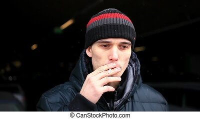 Young man smoking cigarette begins to cough after Smoking Cigarette while snowing. HD, 1920x1080