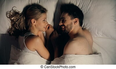 Sweet Nothing - Close up of young couple lying in bed facing...