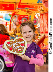 child with gingerbread heart. mother's day - a child holds a...
