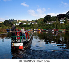 Two men steering a barge into a boatyard near Llangollen -...