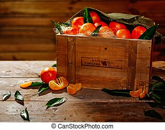 Wooden crate with tasty tangerines on a table