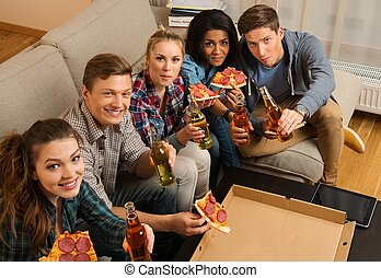 Group of multi-ethnic friends with pizza and bottles of...