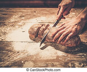 Man cutting homemade bread on a table