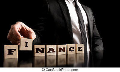 Arranging Small Wooden Blocks with word Finance - Financial...