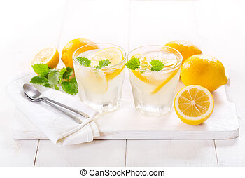 glasses of lemonade with fresh fruits on wooden table