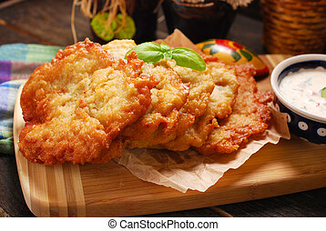 potato cakes lying on wooden board with bowl of vegetable...