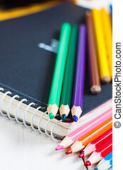 sketchbook and colorful pencils on the table. - sketchbook...