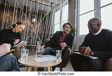 Executives having a meeting indoors - Relaxed young...