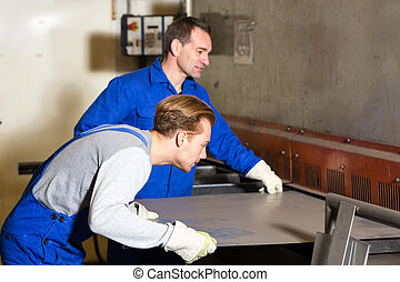 Two workers bending sheet metal with large machine - Two...