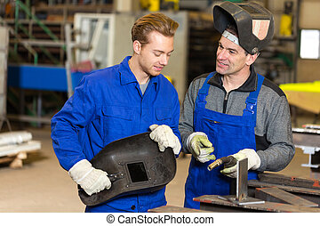 Instructor teaching trainee how to weld metal - Instructor...