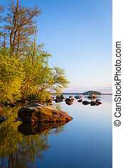 Calm lakeside at sunset and rocks on the water