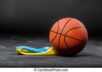 Basketball ball and flag - Basketball ball lying on a black...