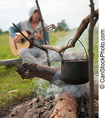 cooking fresh food in cauldron at camp on open fire -...