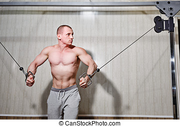 Man trains in gym - Man trains biceps and triceps in the gym...