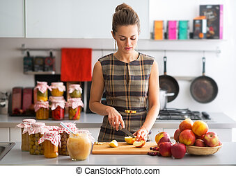 Young housewife cutting apple in kitchen