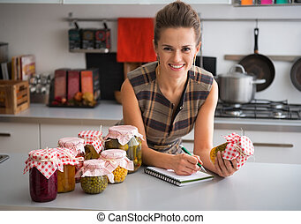 Housewife writing in notepad among jars of pickled vegetables in