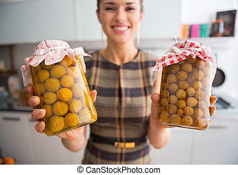 Closeup on young housewife showing jars with homemade...