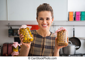 Portrait of happy young housewife showing jars with homemade...