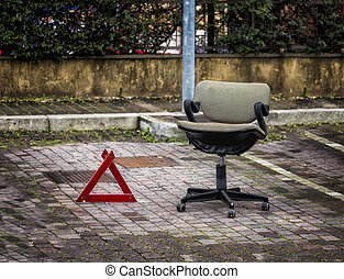 Chair and Danger Triangle Sign on a City Pavement