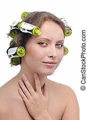 Beatiful woman with hair rollers in curls on white