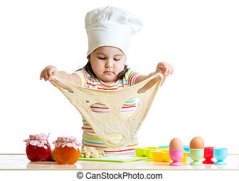 Little girl in cap of the cook playing with dough - Little...