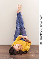 Beauty with mobile phone. Beautiful young woman holding mobile phone while lying on the floor and leaning her legs at the wall