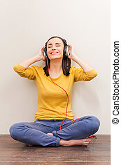 Dissolving in lovely music. Beautiful young woman in headphones keeping eyes closed while sitting on the floor against brown background