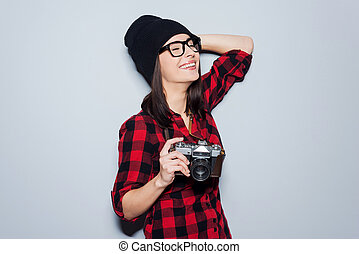 She is fond of shooting.  Beautiful young woman in headwear and glasses holding camera and keeping eyes closed while standing against grey background