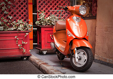 Bright Orange Scooter parked by rustic red plant boxes.