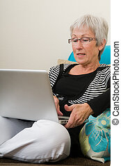 Senior woman working on a laptop, sitting relaxed on the...