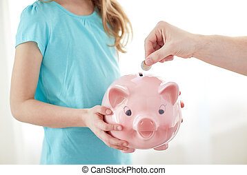 close up of girl with piggy bank putting coin - family,...