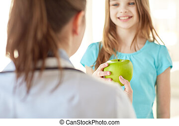 close up of doctor giving apple to happy girl - health care,...