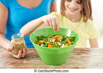 close up of happy family cooking salad in kitchen - food,...