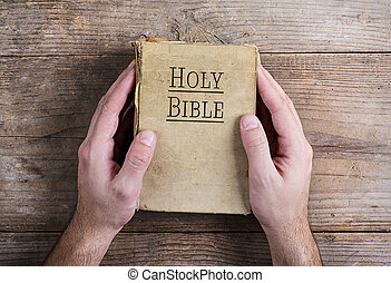 Bible and praying hands - Hands holding Bible on a wooden...