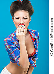 young girl with bra on pin up style eating a Cake
