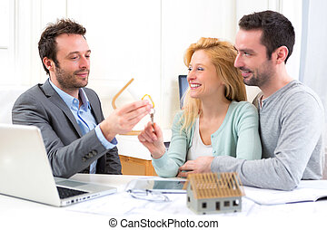Real estate agent delivers keys of new house to young couple...