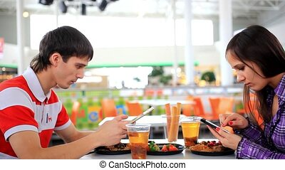 Young couple using tablet computer  and phone in cafe until have a lunch. HD. 1920x1080