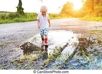 Boy in a puddle - Little boy playing outside in a puddle